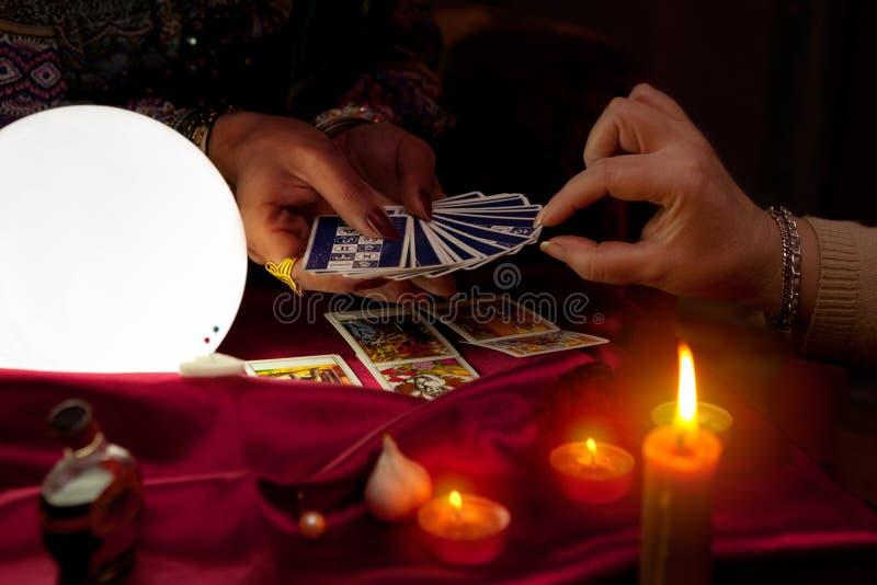 Carte di tarocchi della tenuta dell'indovino della donna in sue mani immagine stock