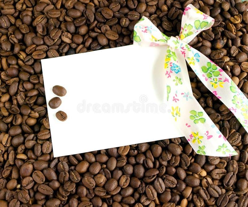 Carte et arc blancs sur un fond des grains de café photographie stock