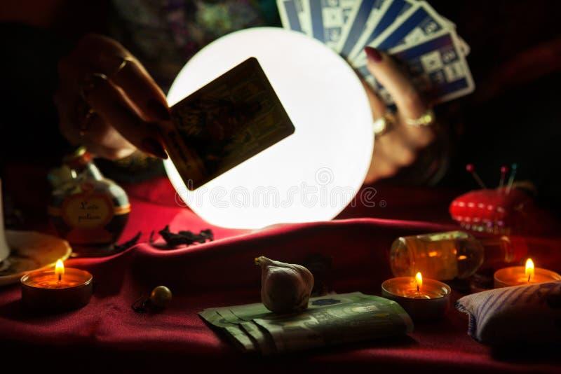 Carte et boule de cristal de tarot derrière elle images stock