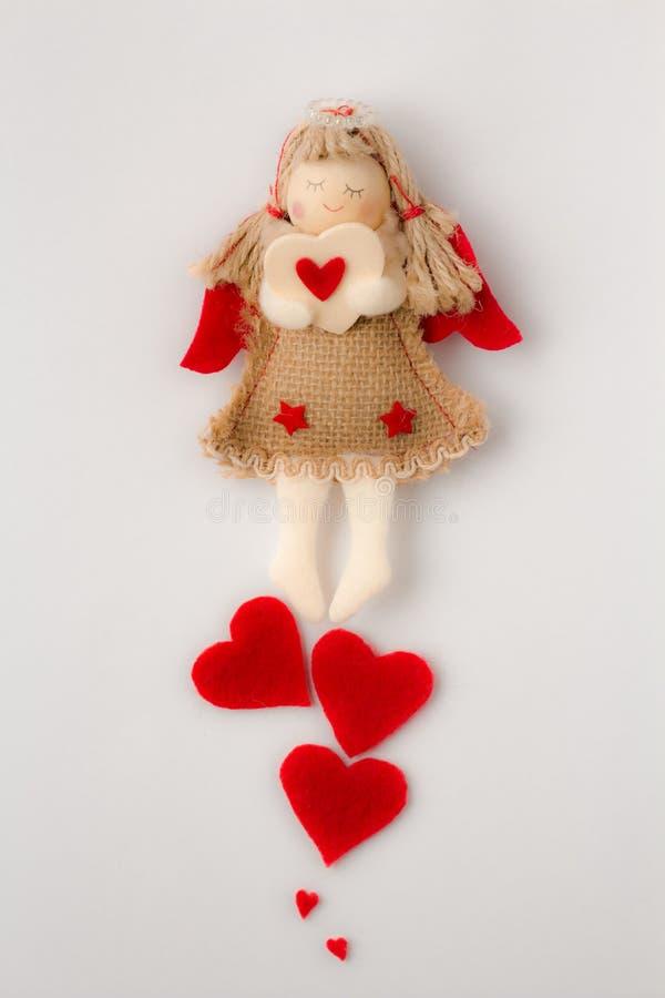 Carte faite maison d'ange avec un coeur dans des mains sur un fond blanc images stock
