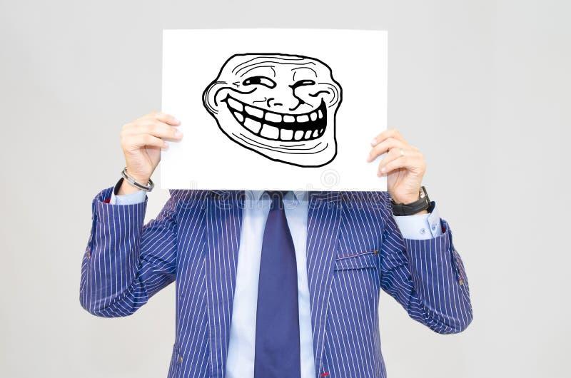 Carte hoding d'homme d'affaires avec le visage de troll sur le fond gris photographie stock
