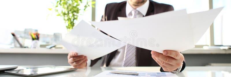 Carte maschii della tenuta del braccio al primo piano del posto di lavoro dell'ufficio immagine stock libera da diritti