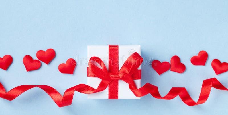 Carte ou bannière de Saint Valentin Cadeau ou coeur de boîte et rouge actuel sur le fond bleu Configuration plate photo libre de droits