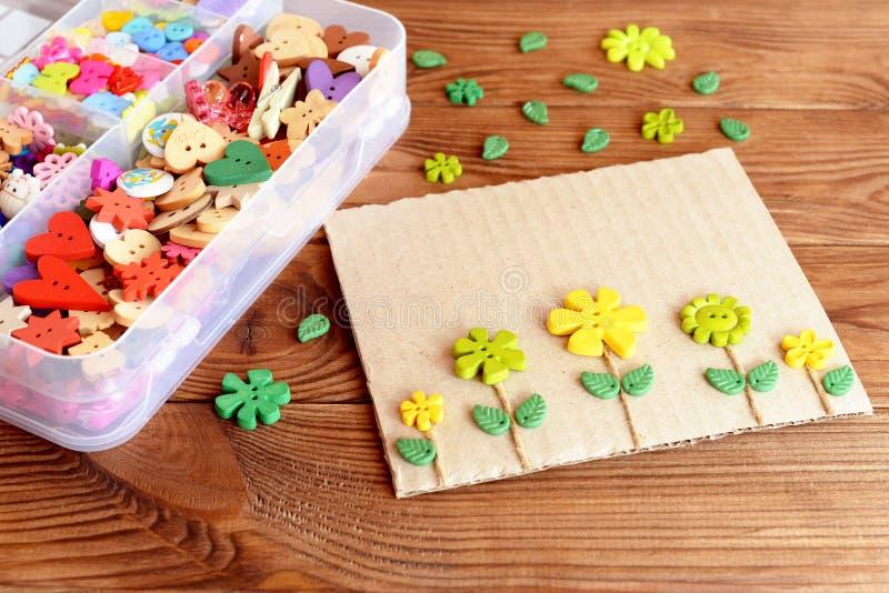 Carte postale faite de carton, boutons et corde Une boîte de boutons colorés sur un fond en bois brun image stock