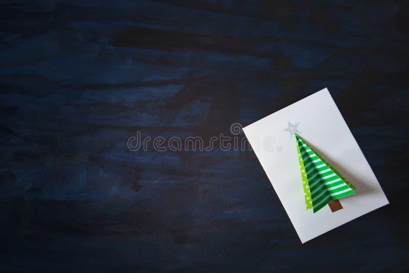 Carte postale faite maison de Noël sur le fond foncé Arbre de Noël vert sur le blanc sur la carte postale image libre de droits