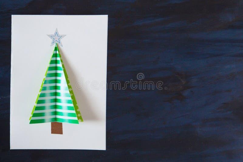 Carte postale faite maison de Noël sur le fond foncé Arbre de Noël vert sur le blanc sur la carte postale image stock