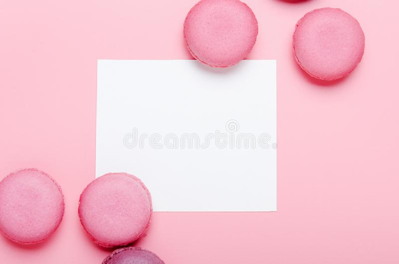 Carte pour une inscription, félicitations, blanc des textes sur un fond rose avec un biscuit rose de macaron Salutation douce photographie stock
