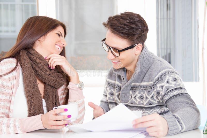 Carte sorridenti della lettura delle coppie e caffè bevente immagine stock