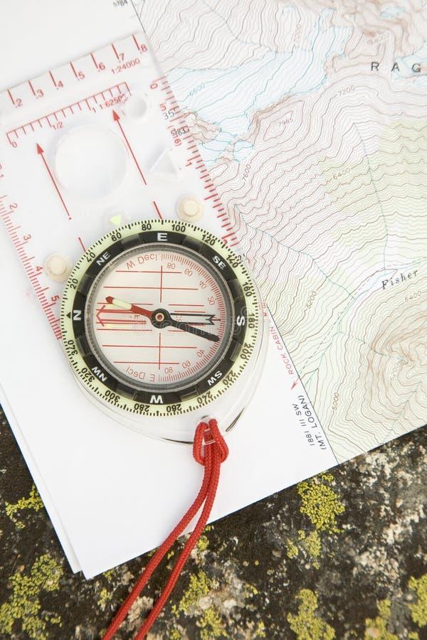 Carte topographique et boussole sur la roche couverte de lichen Navigation routefinding dans la région sauvage La carte est publi photos libres de droits