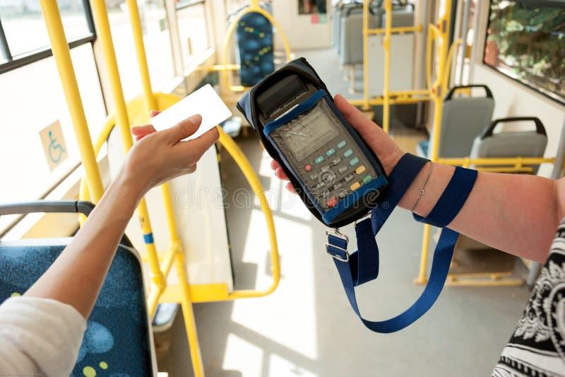Carte umane della plastica della tenuta della mano Il passeggero paga il prezzo nel trasporto pubblico Terminale di pagamento, le immagine stock libera da diritti