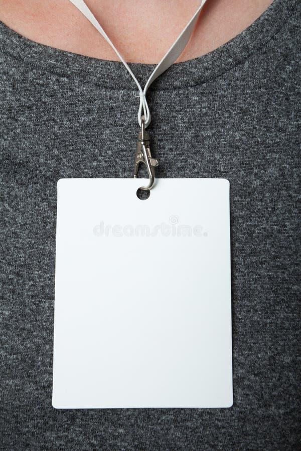 Carte vide d'identification sur une lanière sur un fond uniforme gris, verticalement Maquette d'?tiquette de nom photo stock