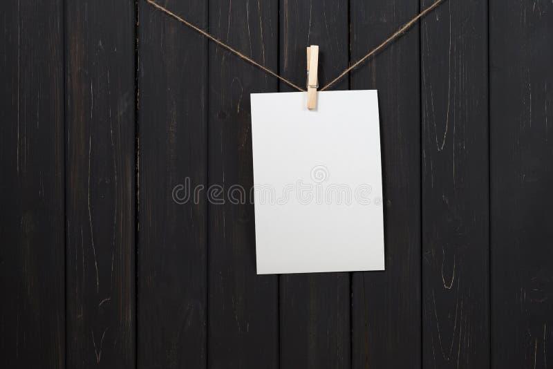 Carte vierge de livre blanc accrochant sur des pinces à linge image stock