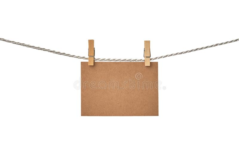 Carte vierge de papier de métier accrochant sur la corde à linge sur le fond blanc photographie stock