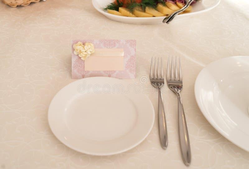 Carte vierge pour des invités près du plat vide blanc sur la table images stock