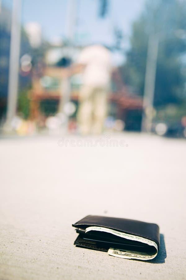 Carteira: A carteira coloca no passeio com o homem no fundo fotografia de stock