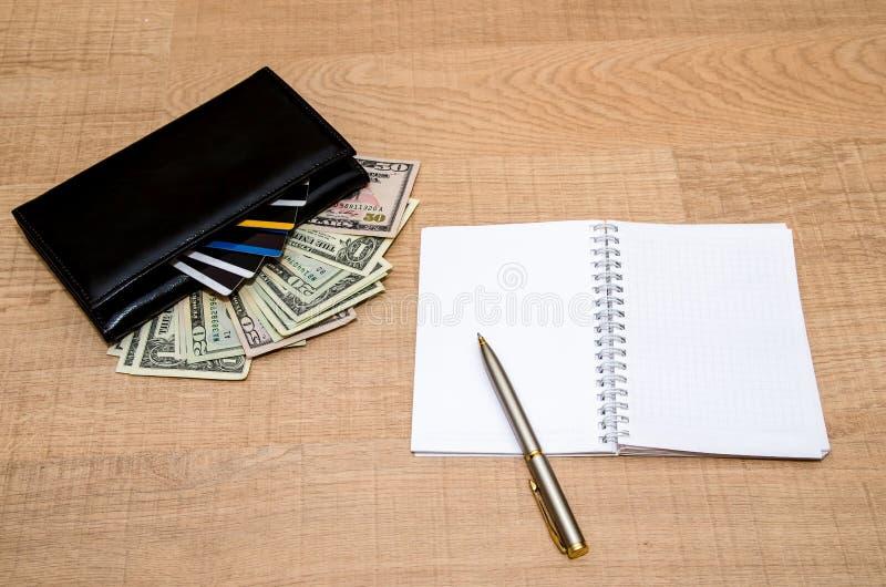 Carteira com dinheiro, cartões de crédito e bloco de notas imagens de stock