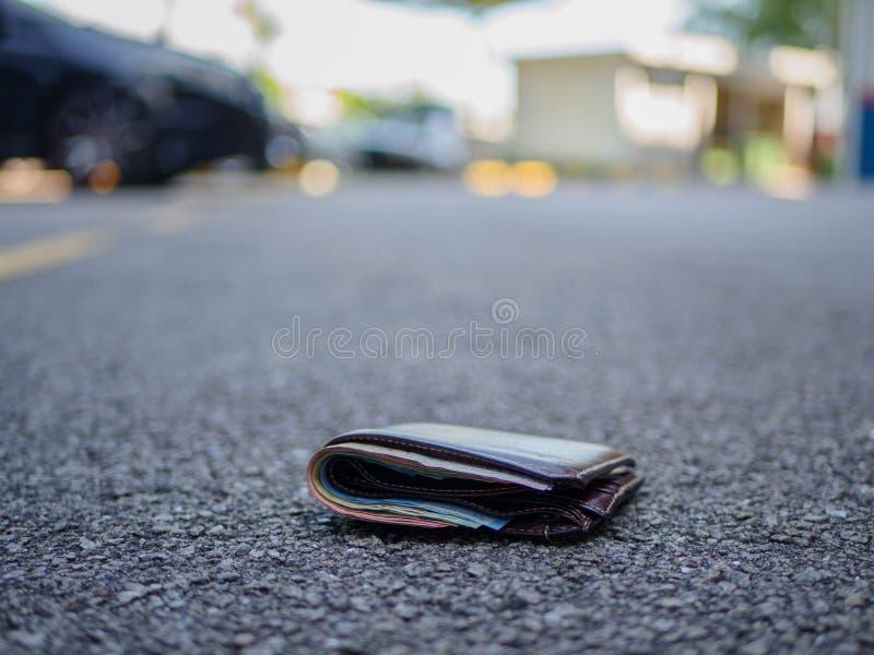 Carteira com gota do dinheiro na rua fotografia de stock