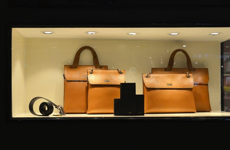 A carteira de couro luxuosa da correia da bolsa na janela da loja iluminou-se acima por luzes conduzidas fotografia de stock