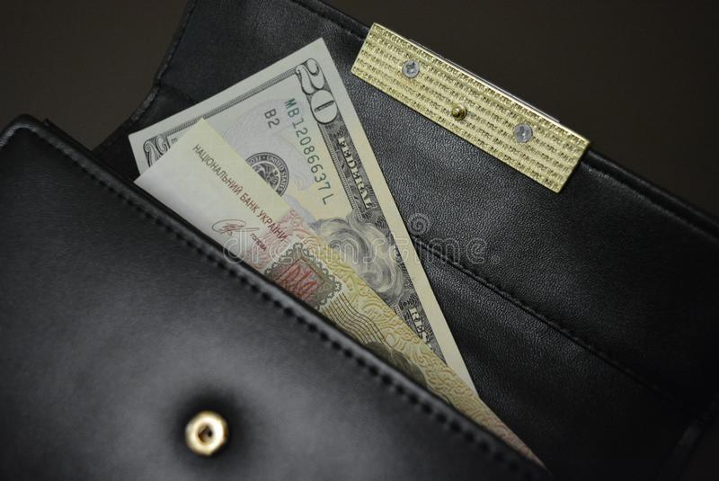 Carteira de couro preta com dinheiro nele em um fundo marrom do resíduo metálico Cédulas 20 vinte dólares americanos e 100 cem Uk fotos de stock royalty free
