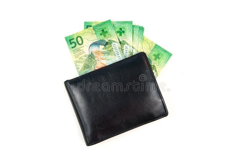 Carteira de couro preta com francos suíços no fundo branco imagens de stock royalty free