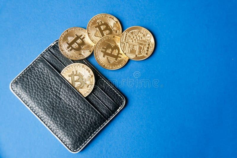 Carteira de couro preta em um fundo azul com diversas moedas de ouro dos bitcoins que caem fora de seus bolsos fotos de stock royalty free