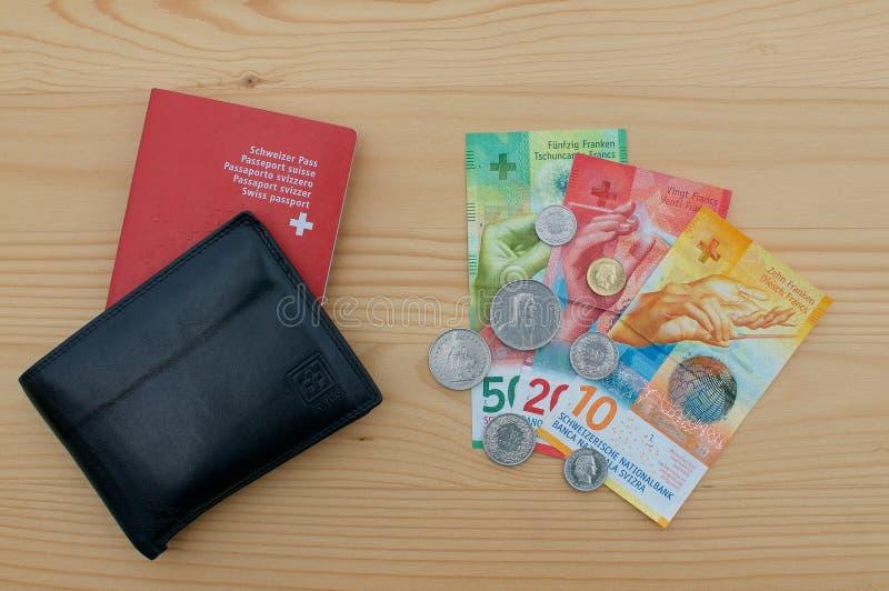 Carteira preta com passaporte suíço e moeda suíça imagem de stock