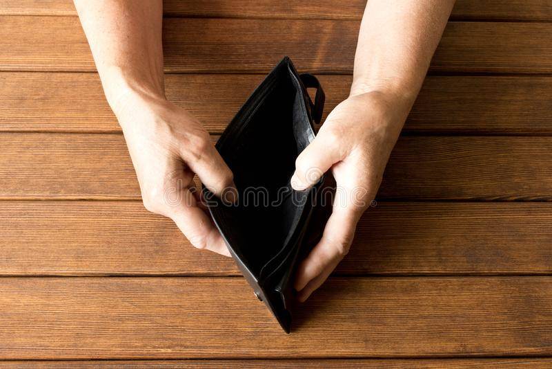 Carteira vazia nas mãos de um homem idoso em uma tabela de madeira T imagens de stock