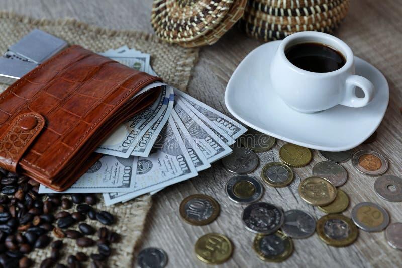 Carteira vermelha com d?lares americanos, as v?rias moedas estrangeiras e a x?cara de caf? na tabela fotografia de stock royalty free