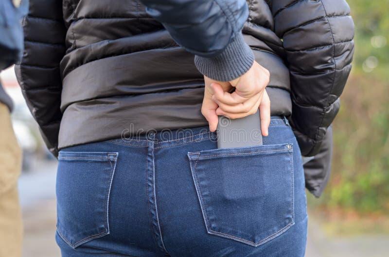 Carteirista que alcança para um móbil em um bolso traseiro imagem de stock royalty free