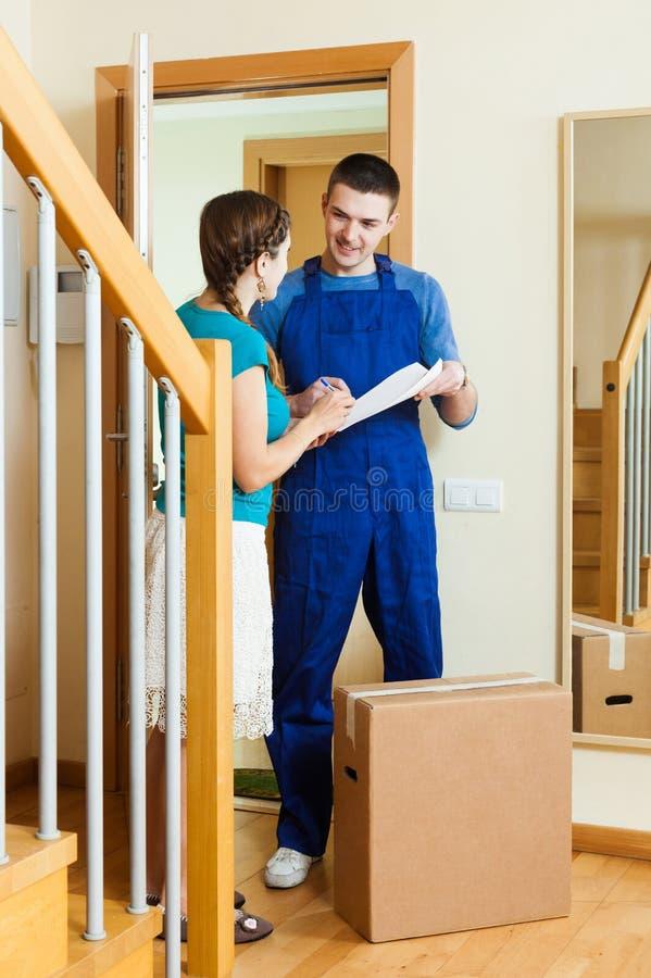 Carteiro no pacote entregado uniforme à menina fotografia de stock