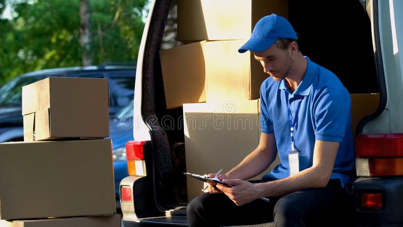 Carteiro trabalhador que verifica uma quantidade de caixas, trabalho responsável, inventário fotos de stock royalty free