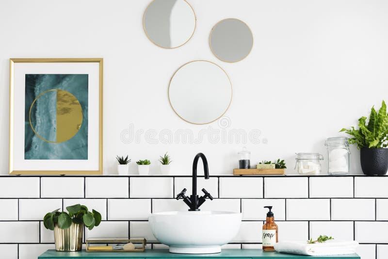 Cartel al lado de los espejos redondos sobre el lavabo y la planta en el interior blanco del cuarto de baño Foto verdadera fotos de archivo libres de regalías