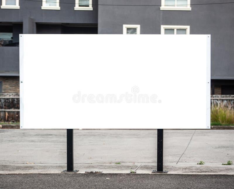 Cartel de la cartelera en el borde de la carretera con mofa en blanco del blanco encima del área imagenes de archivo