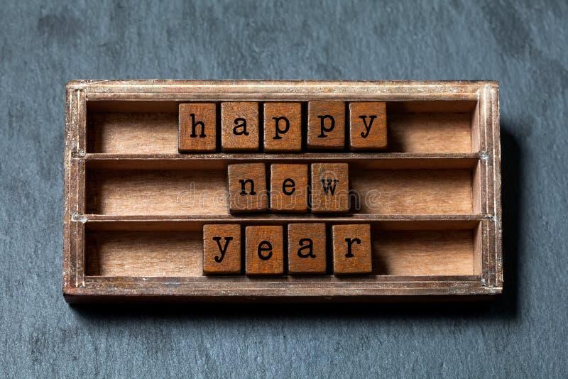 Cartel de la invitación de la tarjeta de felicitación de la Feliz Año Nuevo Caja del vintage, cubos de madera con las letras del  foto de archivo libre de regalías