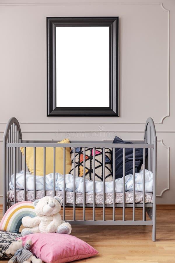 Cartel de la maqueta en marco negro en la pared gris del interior del sitio del bebé con el pesebre con las almohadas, visión ver foto de archivo