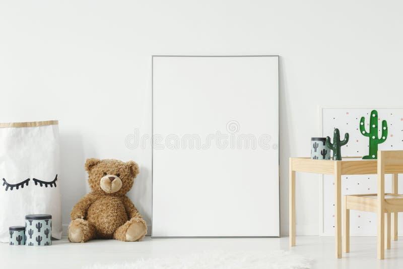 Cartel de la maqueta, oso de peluche y cesta del material colocados en el floo imagen de archivo libre de regalías