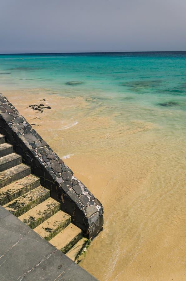 Cartel de la naturaleza Enarene la playa con agua clara del océano y el stai de piedra imagen de archivo