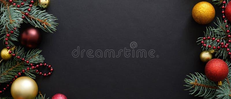Cartel de Navidad. Fondo negro de Navidad con ramas de abetos, bolas doradas y rojas, guirnaldas. Marco de Navidad, tarjeta de fel foto de archivo libre de regalías