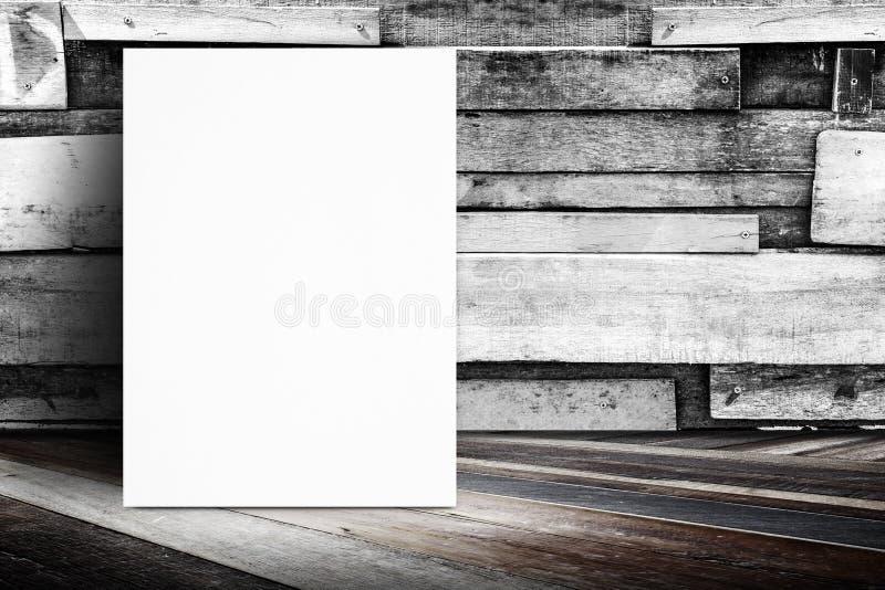 Cartel en blanco que se inclina en la pared de madera del tablón y el piso de madera diagonal, imagenes de archivo
