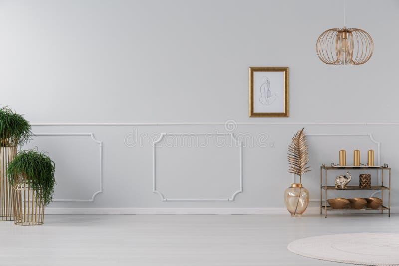 Cartel en la pared blanca con el moldeado en interior de la sala de estar con la lámpara y las plantas del oro Foto verdadera fotos de archivo