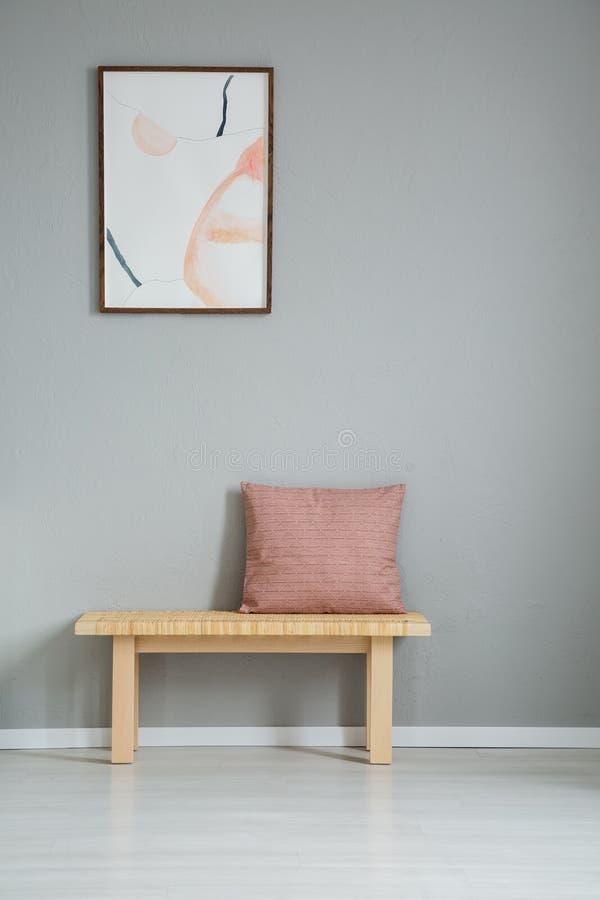 Cartel en la pared gris sobre banco de madera con la almohada rosada en interior simple del apartamento Foto verdadera fotos de archivo libres de regalías
