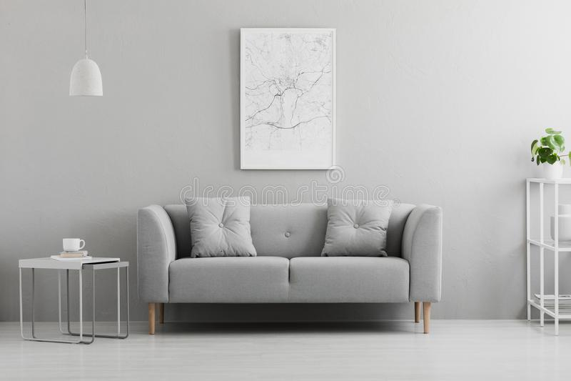 Cartel sobre el sofá gris en interior mínimo de la sala de estar con la tabla antedicha de la lámpara Foto verdadera imagen de archivo