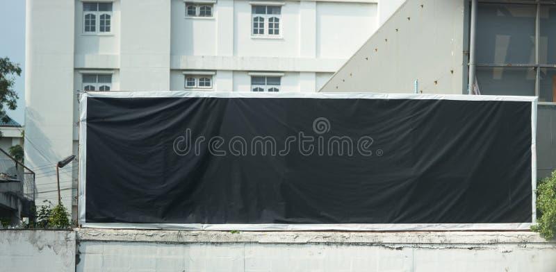 Cartelera ascendente falsa negra en la cerca en fondo de la ciudad de la falta de definición foto de archivo libre de regalías