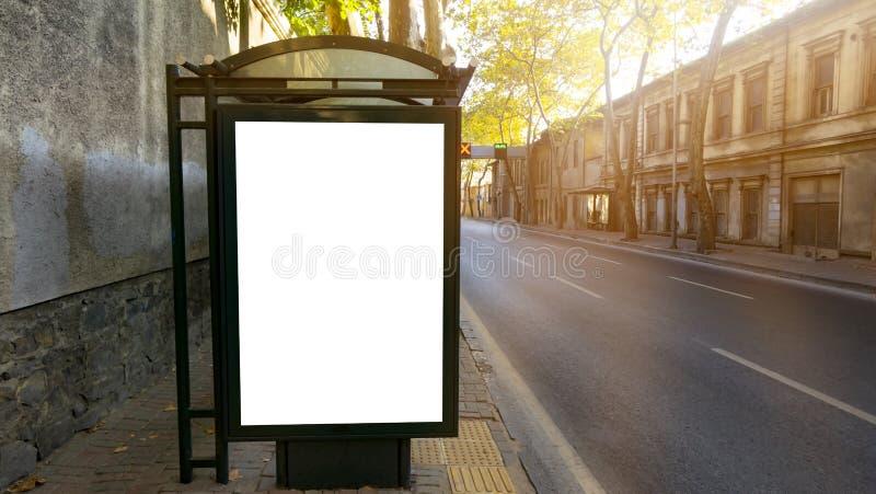 Cartelera blanca en blanco vertical en la parada de autobús en la calle vieja de la ciudad En los edificios y el camino del fondo imagenes de archivo
