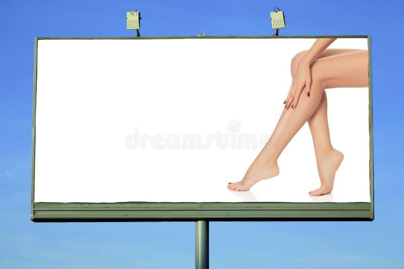 Cartelera con las piernas femeninas foto de archivo libre de regalías