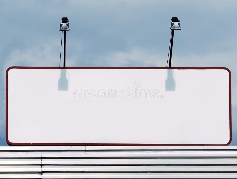 Cartelera de publicidad blanca del espacio en blanco con dos proyectores para iluminarla contra un cielo nublado del verano imagen de archivo libre de regalías