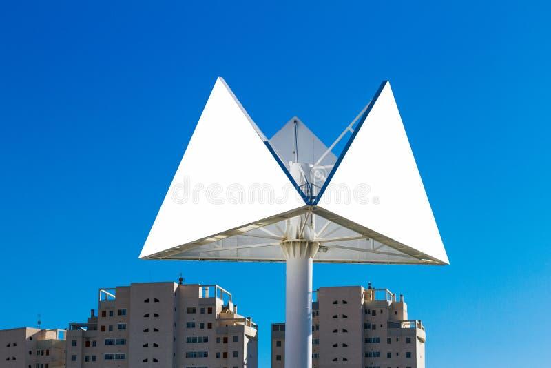 Cartelera del triángulo o cartel de la publicidad con el fondo de la ciudad y del cielo azul imagenes de archivo
