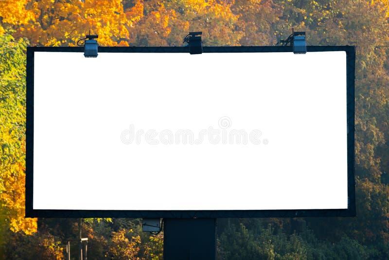 Cartelera en blanco con el copyspace rodeado por el bosque al aire libre adentro fotos de archivo