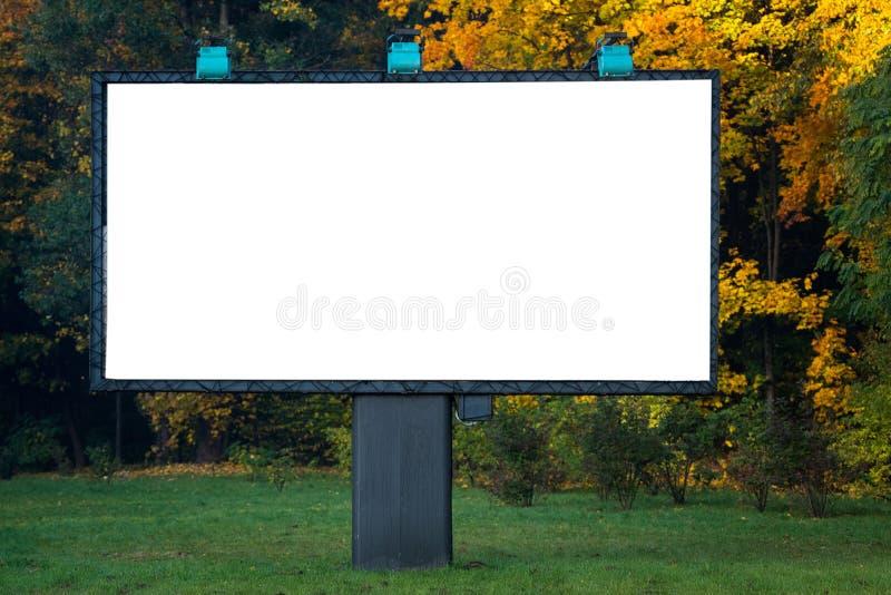 Cartelera en blanco con el copyspace rodeado por el bosque al aire libre adentro imagen de archivo