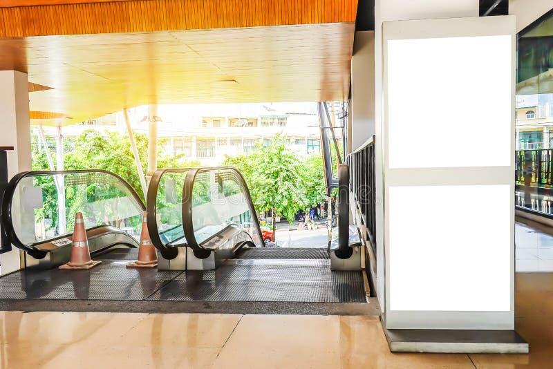 Cartelera en blanco grande cerca de la escalera móvil en un supermercado con el sitio fotos de archivo